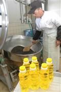 黄金色に輝くヒマワリ油(手前)の搾油作業に追われる栽培農家